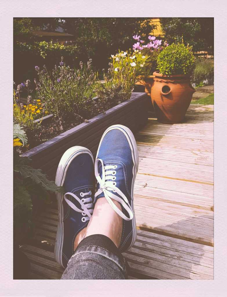 feet wearing blue Vans trainers, on a deck with flowers and plants